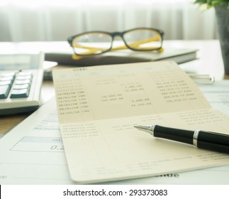 Accountants desk with pen and bank book. selective focus.