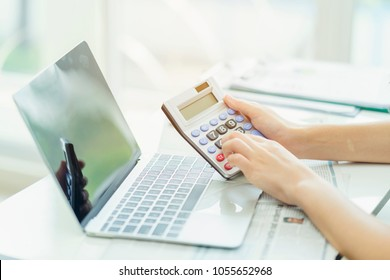 Accounting analyst calculate break even point by using financial report for banking investment. Using calculator and computer laptop to collect financial data to analyse profit for executive decision