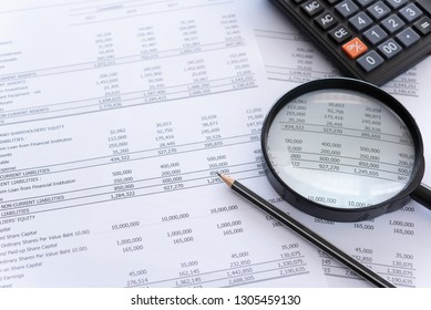 accounting audit concept. calculator and magnifying glass on financial statement and balance sheet annual on auditor's desk.