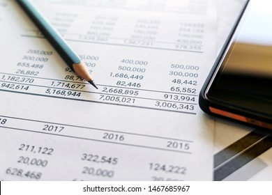 accounting audit concept. Pencil and mobile phone on financial statement and balance sheet annual on auditor's desk.