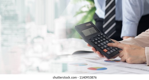 Accounting Business Calculation Concept. Business women using a calculator to reviewing financial statement.