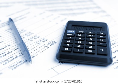 Accounting business concept. Close-up calculator with pen at financial report background.