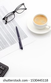 Accounting business concept. Desktop with cup of coffee, calculator, glasses, notepad and spreadsheet. Copy space composition. Selective focus