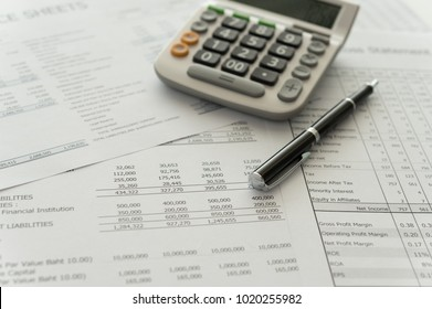 accounting business concept.  pen, calculator, financial statement on accountant's desk.