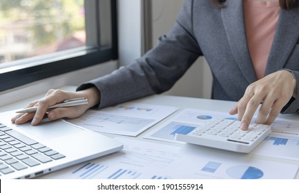 Accounting businesswomen are calculating income-expenditure and analyzing real estate investment data, Dedicated to the progress and growth of the company, Financial and tax systems laptop concept.