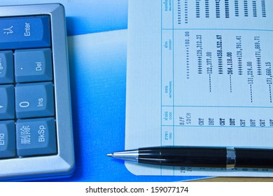 Accounting Calculator, pen and  Bank account on table