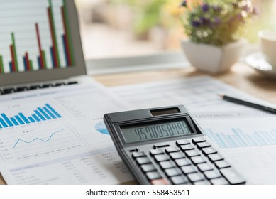 accounting concept. calculator on report summarizes the results of business operations and computer on desk of investor at home in morning.