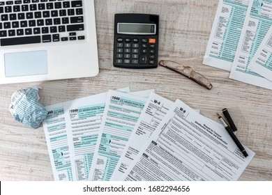 accounting concept. us 1040 tax form with pen, dollar and laptop at office. tax time.