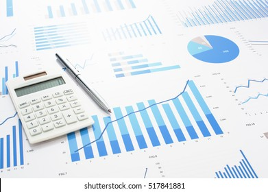 Accounting data, charts, calculator and pen. Many charts and graphs. Reflection background.