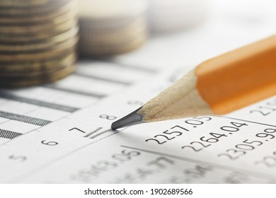 Accounting document with pencil, money, coins and checking financial chart. Concept of banking, financial report and financial audit.