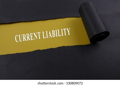 Accounting and finance concept, word current liability on torn paper.