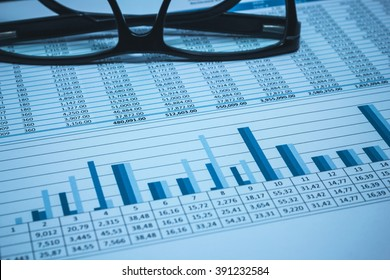 Accounting financial bank banking account stock spreadsheet data with glasses in blue