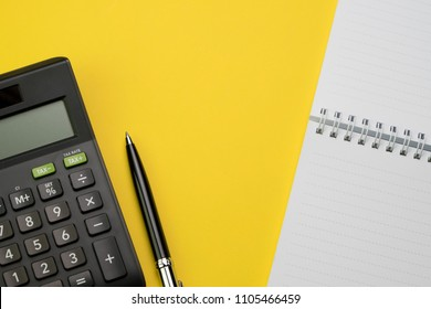Accounting, financial concept, flat lay or top view of black pen, calculator with white notepad on vivid yellow background table with blank copy space, math, cost, tax or investment calculation.