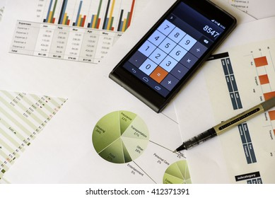 Accounting and personal finance - printed sheets with graphs and pie charts, pen and electronic calculator - income, expenses and totals