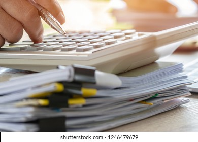 Accounting planning budget concept : Accountant hand calculate financial report and counting on calculator for checking financials data analyzing documents paperwork in office on busy desk