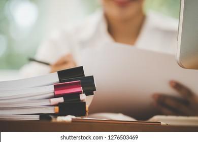 Konzept für die Erstellung des Haushaltsplanberichts: Geschäftsfrauenbüros überprüfen die Arbeit, um Dokumente zu arrangieren, die noch nicht fertig sind Stapel von Dokumenten mit Schreibstift auf einem geschäftigen Büro mit PC-Computer.