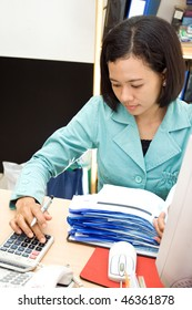 accounting staff working on receipt with calculator
