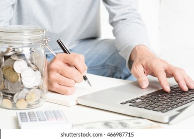 Accounting and technology. Man analyzing investment, with laptop computer, calculator, diary, money on table. Financial adviser working.