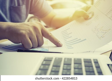 accounting,financial,close up of business man hand working on laptop computer pointing with business graph information diagram on wooden desk as concept,vintage,selective focus