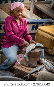ACCRA, GHANA - APRIL 18, 2015: An African woman cuts fish in a local fish market.  Post crop vignetting and highlighting focus attention on the subject.