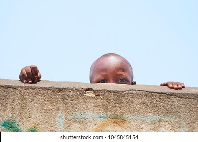 Accra, Ghana - FEB 2017: An African child looks in camera from behind a wall.