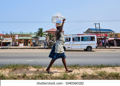 Accra, Ghana - Feb 26, 2017: A woman who sells water on the street carries her load balanced on her head.