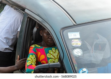 ACCRA, GHANA - JAN 8, 2017: Unidentified Ghanaian woman in colored dress in the front seat of the car. People of Ghana suffer of poverty due to the economic situation