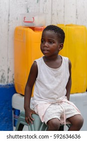ACCRA, GHANA - Jan 8, 2017: Unidentified Ghanaian little girl in white suit sits on a plastic chair at the local market. People of Ghana suffer  poverty due to the economic situation