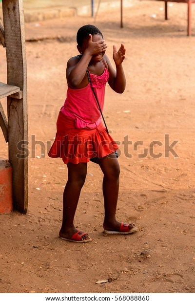 ACCRA, GHANA - JAN 8, 2017: Unidentified Ghanaian woman in red dress closes her face with her hand. People of Ghana suffer of poverty due to the economic situation