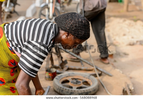 ACCRA, GHANA - JAN 8, 2017: Unidentified Ghanaian woman bends down for something on the street. People of Ghana suffer of poverty due to the economic situation