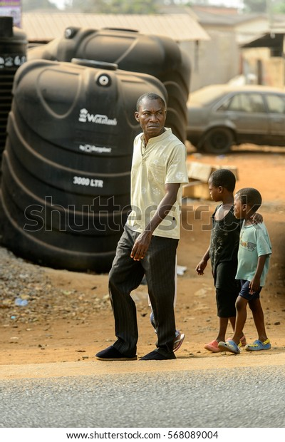 ACCRA, GHANA - JAN 8, 2017: Unidentified Ghanaian man and couple of kids behind walk on the street . People of Ghana suffer of poverty due to the economic situation