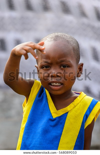 ACCRA, GHANA - JAN 8, 2017: Unidentified Ghanaian  little boy in yellow and blue shirt raises his hand. Children of Ghana suffer of poverty due to the economic situation