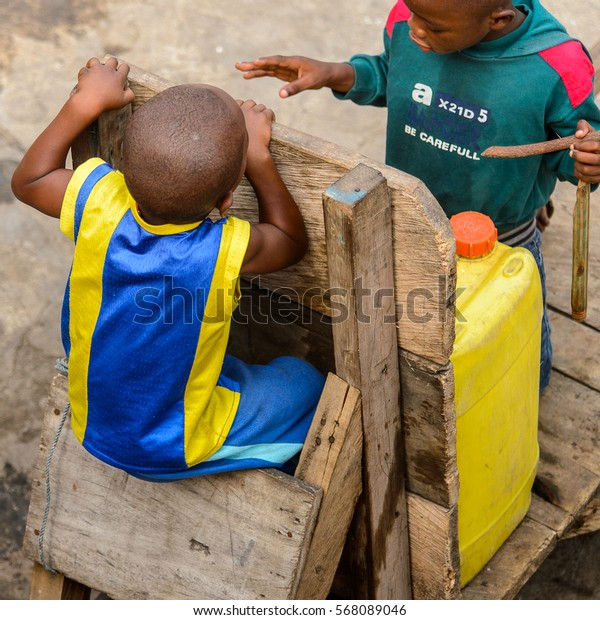 ACCRA, GHANA - JAN 8, 2017: Unidentified Ghanaian little boy in yellow and blue shirt seats on the wooden cart. Children of Ghana suffer of poverty due to the economic situation