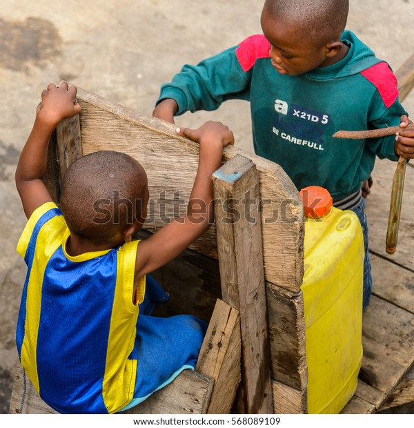 ACCRA, GHANA - JAN 8, 2017: Unidentified Ghanaian little boy in yellow and blue shirt seats on the cart. Children of Ghana suffer of poverty due to the economic situation