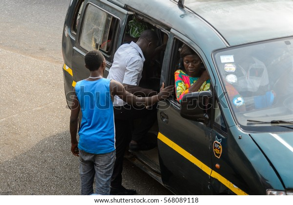 ACCRA, GHANA - JAN 8, 2017: Unidentified Ghanaian men from behind get in the car. People of Ghana suffer of poverty due to the economic situation