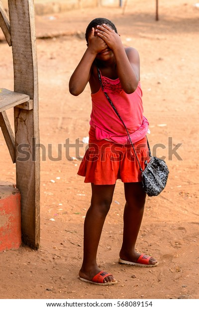 ACCRA, GHANA - JAN 8, 2017: Unidentified Ghanaian woman in red dress closes her face with her hands. People of Ghana suffer of poverty due to the economic situation