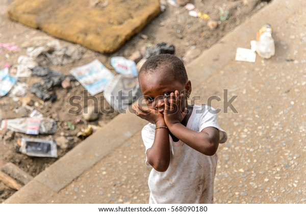 ACCRA, GHANA - JAN 8, 2017: Unidentified Ghanaian little girl in dirty white dress  on the street. Children of Ghana suffer of poverty due to the economic situation