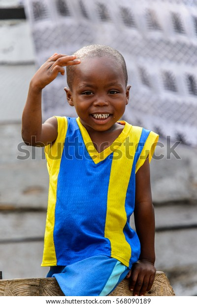 ACCRA, GHANA - JAN 8, 2017: Unidentified Ghanaian  little boy in yellow and blue shirt shows his teeth. Children of Ghana suffer of poverty due to the economic situation