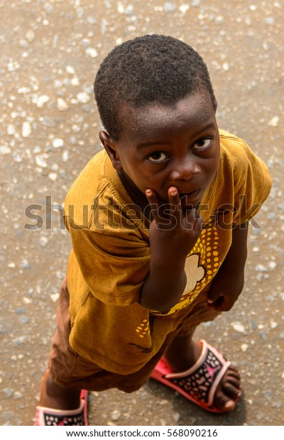 ACCRA, GHANA - JAN 8, 2017: Unidentified Ghanaian little boy in mustard shirt shows his fingers. Children of Ghana suffer of poverty due to the economic situation