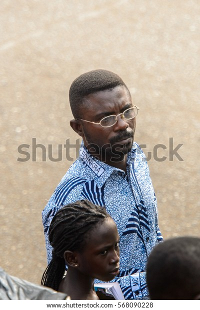 ACCRA, GHANA - JAN 8, 2017: Unidentified Ghanaian man in glasses and colored shirt on the street. People of Ghana suffer of poverty due to the economic situation