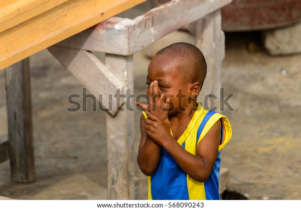 ACCRA, GHANA - JAN 8, 2017: Unidentified Ghanaian little boy in blue and yellow shirt hides his face with his fingers. Children of Ghana suffer of poverty due to the economic situation
