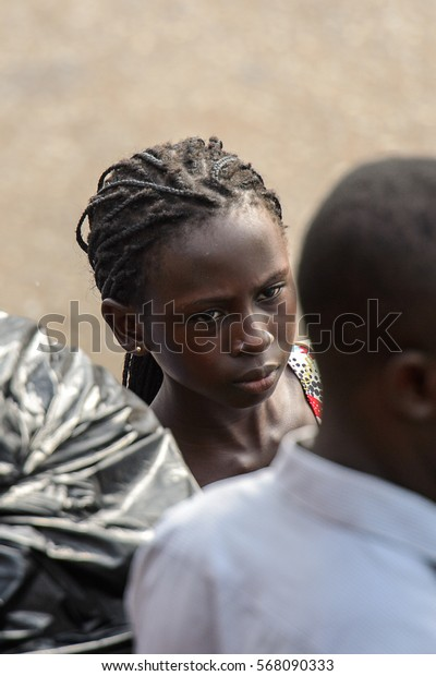 ACCRA, GHANA - JAN 8, 2017: Unidentified Ghanaian beautiful girl wears braids and earing. People of Ghana suffer of poverty due to the economic situation