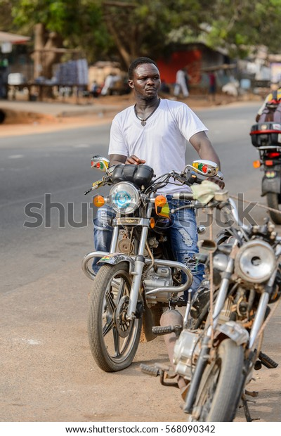 ACCRA, GHANA - JAN 8, 2017: Unidentified Ghanaian man rides the motocycle on the street. People of Ghana suffer of poverty due to the economic situation