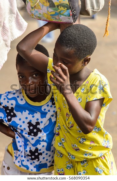 ACCRA, GHANA - JAN 8, 2017: Unidentified Ghanaian two children stand under drying bag and towel . Children of Ghana suffer of poverty due to the economic situation