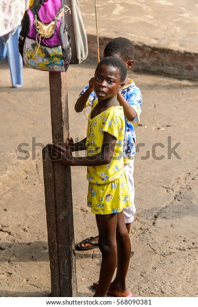 ACCRA, GHANA - JAN 8, 2017: Unidentified Ghanaian little girl in yellow suit stand near wooden pole on the street. Children of Ghana suffer of poverty due to the economic situation