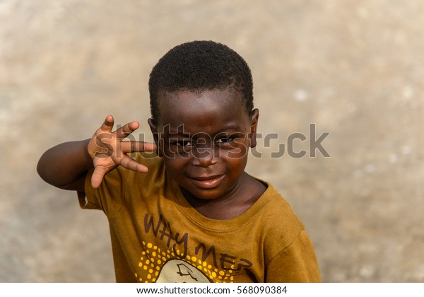 ACCRA, GHANA - JAN 8, 2017: Unidentified Ghanaian little boy in mustard shirt raises his hand. Children of Ghana suffer of poverty due to the economic situation