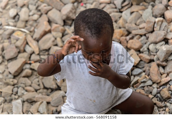 ACCRA, GHANA - JAN 8, 2017: Unidentified Ghanaian beautiful little girl in white shirt puts her fingers into her mouth. Children of Ghana suffer of poverty due to the economic situation