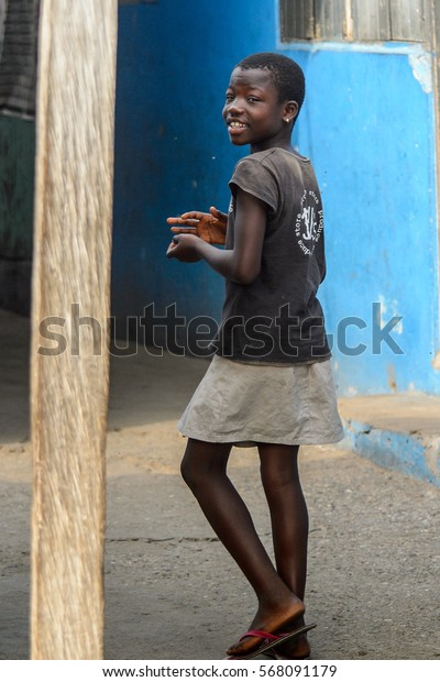 ACCRA, GHANA - JAN 8, 2017: Unidentified Ghanaian girl walks in the street. Children of Ghana suffer of poverty due to the economic situation