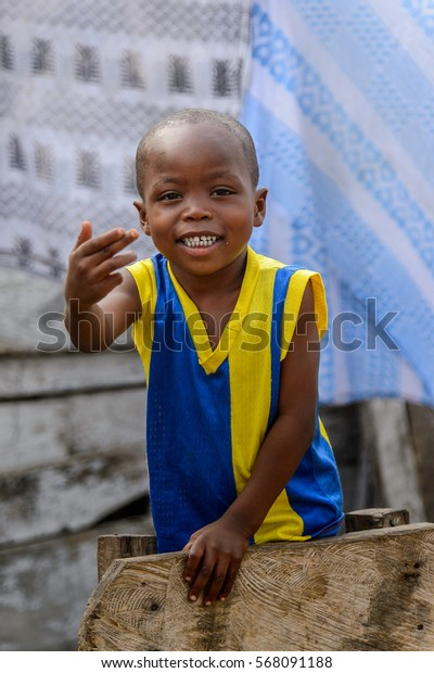 ACCRA, GHANA - JAN 8, 2017: Unidentified Ghanaian little boy in yellow and blue shirt smiles. Children of Ghana suffer of poverty due to the economic situation