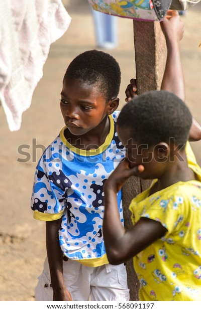 ACCRA, GHANA - JAN 8, 2017: Unidentified Ghanaian  children look away near wooden pole on the street. Children of Ghana suffer of poverty due to the economic situation